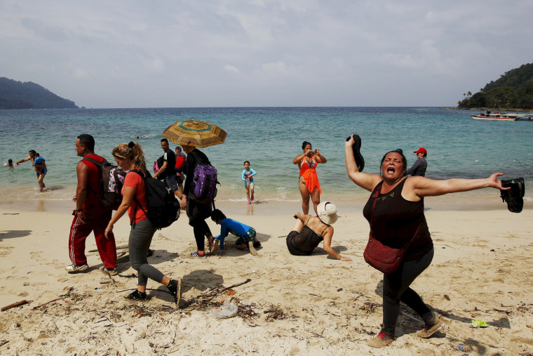 """Image: A Cuban migrant shouts \""""Cuba\"""" after arriving to the beach after crossing the border from Colombia through the jungle as tourist stand by in La Miel, in the province of Guna Yala, Panama"""