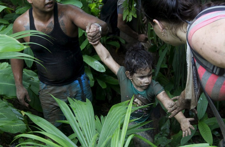 Image: Cuban migrants help a child as they walk down crossing the border from Colombia through the jungle into La Miel, in the province of Guna Yala, Panama