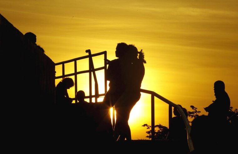 Image: Cubans migrants chat as the sun sets in the town of La Cruz