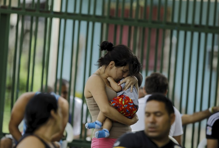 Image: Cuban migrant Sylenay Valle holds her 10 month-old son Yeryko at a shelter in Liberia