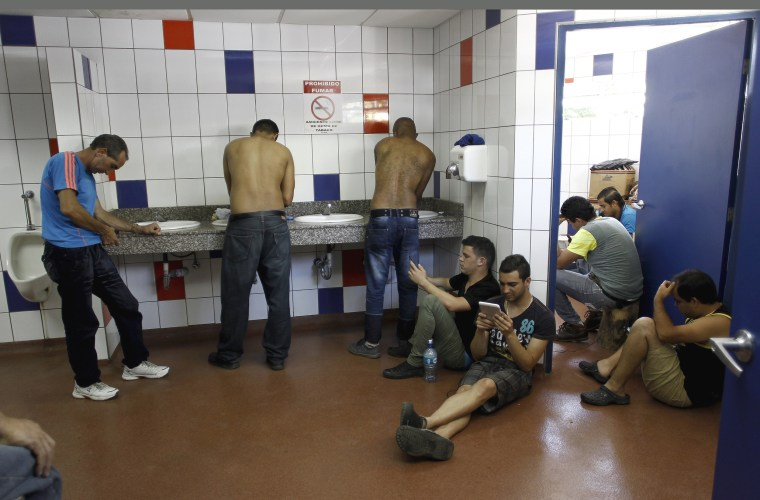 Image: Cuban migrants use their cell phones in a bathroom at the border between Costa Rica and Nicaragua in Penas Blancas