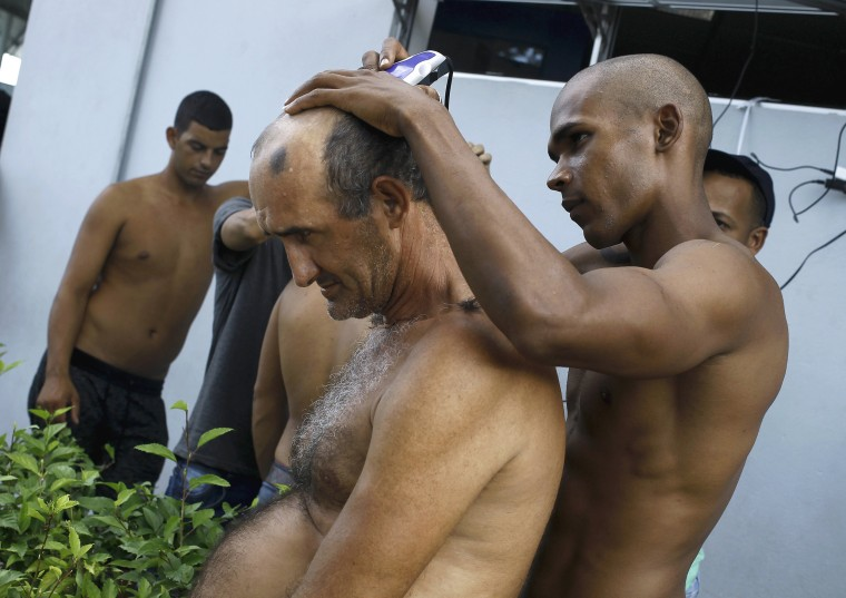 Image: A Cuban migrant cuts the hair of a fellow migrant at the border between Costa Rica and Nicaragua in Penas Blancas
