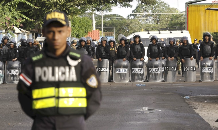 Image: Nicaraguan riot police stand behind a Costa Rican police officer at a border post with Nicaragua in Penas Blancas