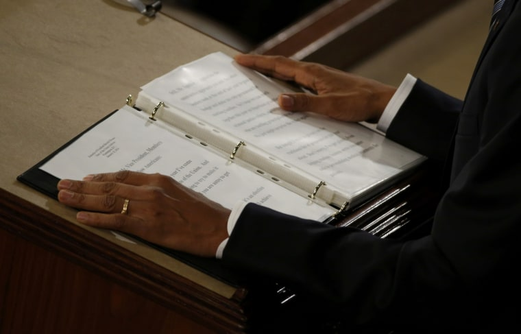 Image: U.S. President Barack Obama places his hands on his notes as he delivers his State of the Union address to a joint session of Congress in Washington