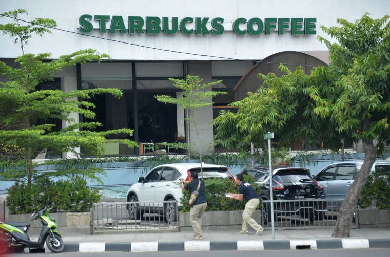Image: Plainclothes police aim their handguns towards suspects outside a cafe