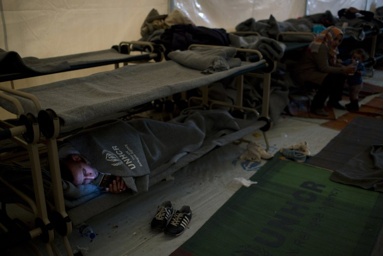 Image: A Syrian man looks on his phone inside the Souda camp in Chios, Greece