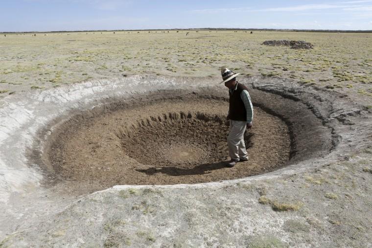 Image: Farmer Sindulfo Fernandez inspects a dried watering hole for llamas in Orinoca