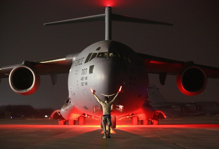 Image: An airman guides a U.S. Air Force C-17 Globemaster after it returned from delivering cargo to Baghdad
