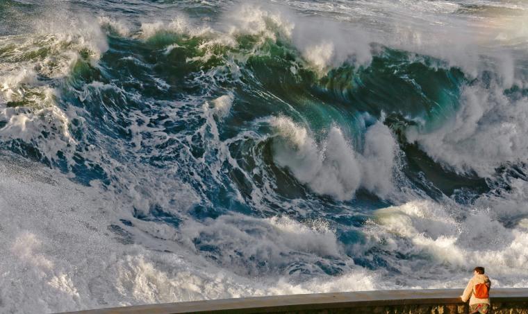 Image: A man watches the huge waves brake at the Paseo Nuevo's promenade