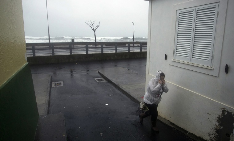 Image: A woman takes cover from heavy rain and wind during the passage of hurricane Alex in Ponta Delgada