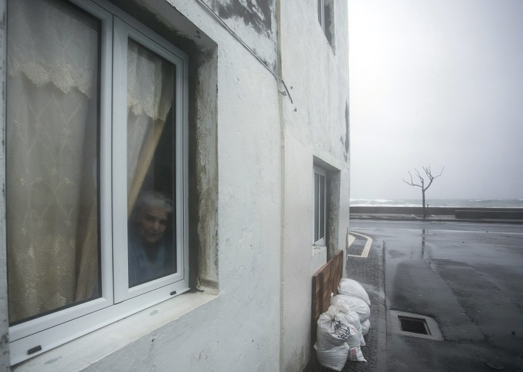 Image: A resident looks out of a window during the passage of hurricane Alex in Ponta Delgada