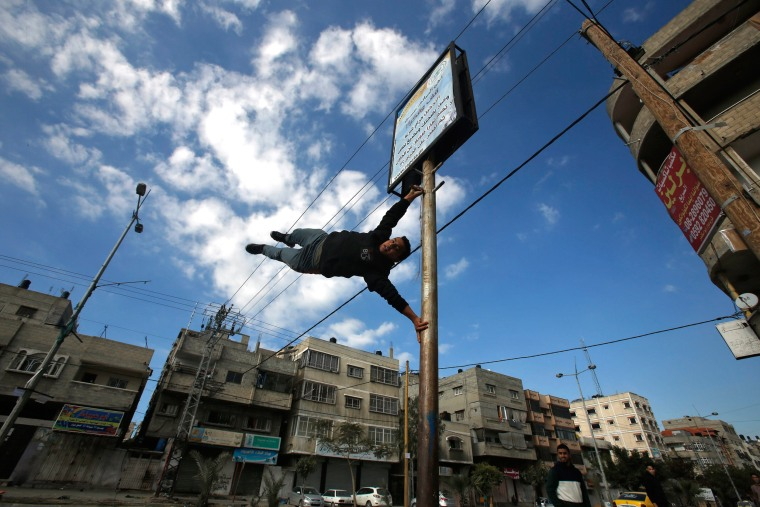 Image: A Palestinian youth demonstrates his parkour skills on a street in Gaza City