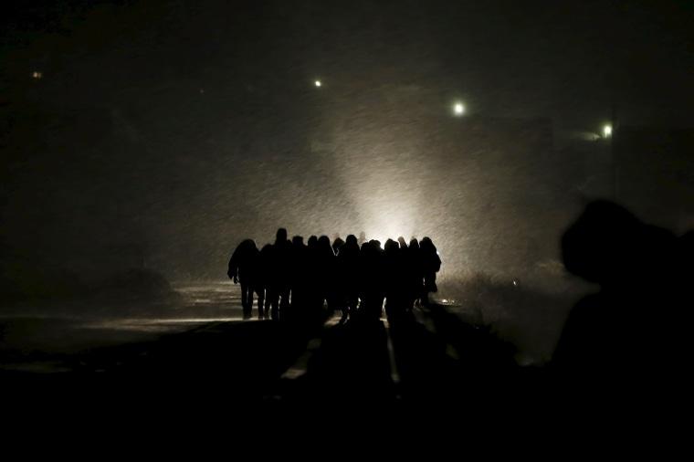 Image: Migrants walk along a road after crossing the border from Macedonia, at Miratovac, Serbia