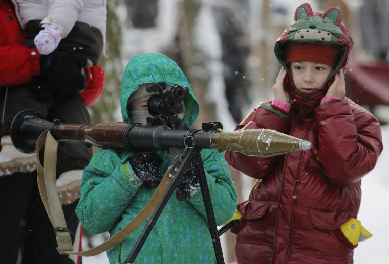 Image: A boy aims an RPG at a weapons exhibition during a military show in St.Petersburg