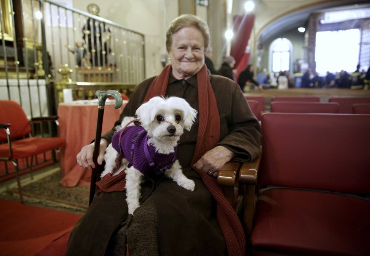 Image: A woman holds her dog as she waits for a mass in San Anton Church in Madrid, Spain