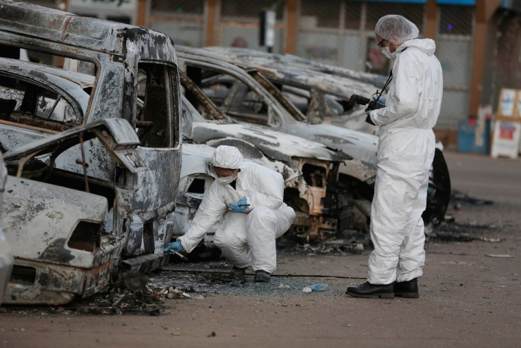 Image: Forensic workers examine burnt out cars