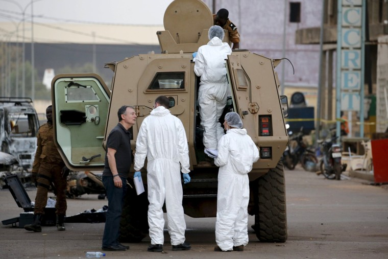 Image: French police (in white) inspect the damage to a Burkinabe armored vehicle