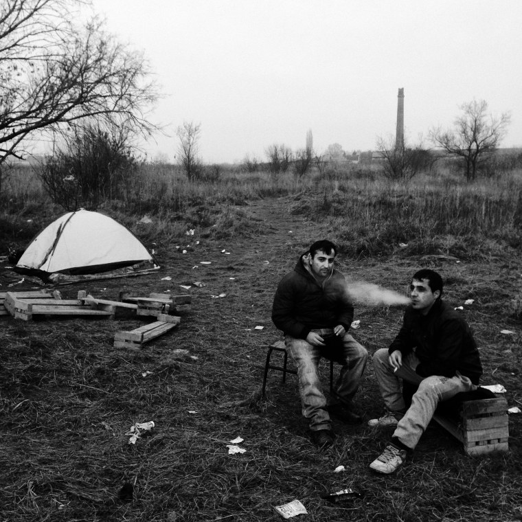 Image: Two men from Iraqi Kurdistan rest close to an abandoned brick factory in Subotica
