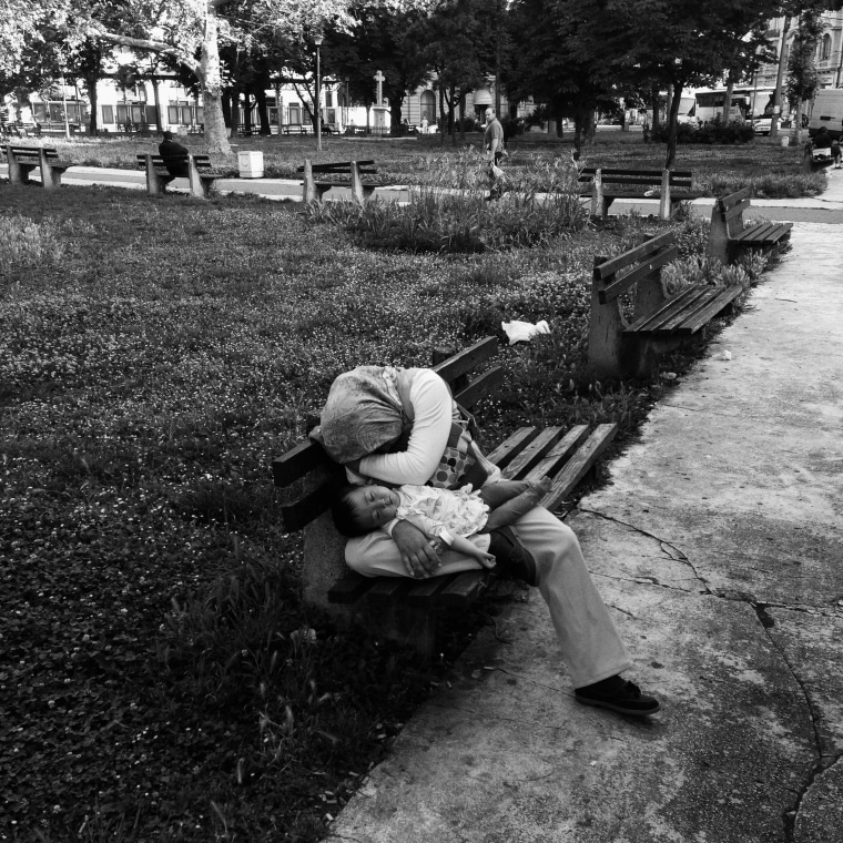 Image: An afghan woman holds a baby in her arms as they sleep on a bench in a park in Belgrade
