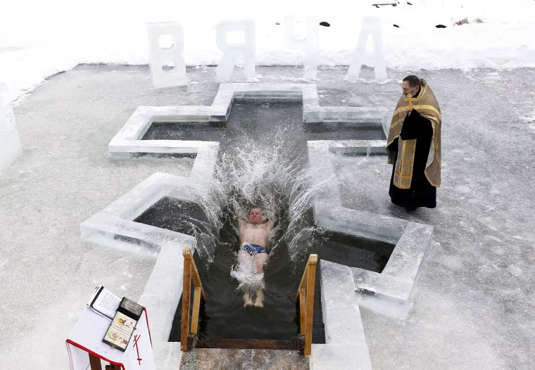 Image: Man dips into the icy waters of a lake as part of celebrations for Orthodox Epiphany on the outskirts of Minsk