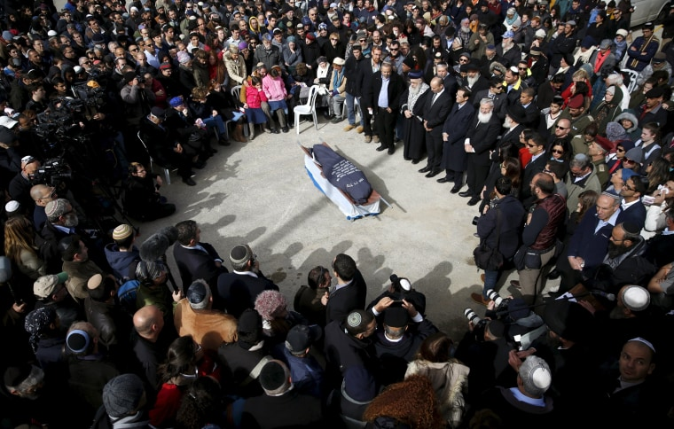 Image: Family and friends surround the body of Dafna Meir, 38, during her funeral at a cemetery in Jerusalem