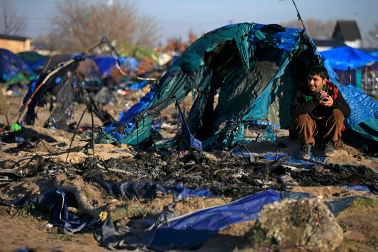 """Image: An Afghan migrant sits in front of a burnt dismantled shelter in the camp known as the """"Jungle"""" in Calais"""