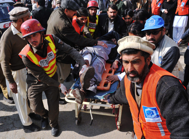 Image: Pakistani rescuers transport an injured man to a hospital