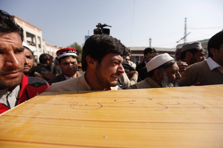 Image:  People move the coffin of a victim