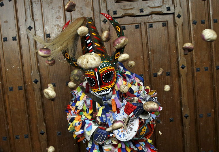 Image: Revellers throw turnips at the Jarramplas, a character who wears a devil-like mask and a colourful costume, as he makes his way through the streets while beating his drum during the Jarramplas traditional festival in Piornal