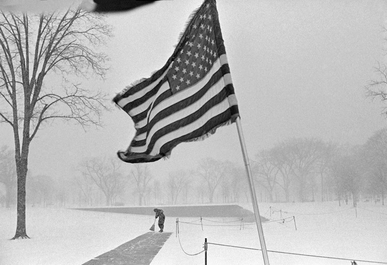 Dale Wey, Cleveland, a Vietnam veteran, sweeps the walkway in front of the Vietnam Veterans Memorial during a snowstorm in Washington on Friday, Feb. 11, 1983. Wey is part of a group of veterans standing vigil at the memorial.
