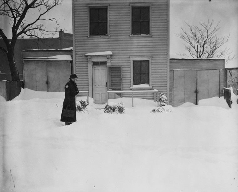 Above, a person stands in front of a house after snow piled up in February, 1936.