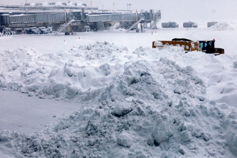 A snow plow is dwarfed by a pile of snow during snow cleanup on the tarmac at Washington's Reagan National Airport, Saturday, Feb. 6, 2010, as a massive snow storm has hit the Washington area, canceling all flights for Saturday.