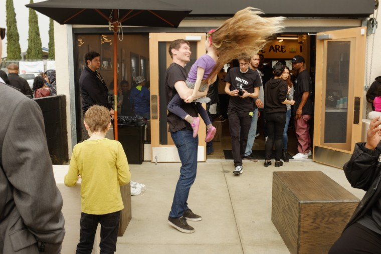 Daniel Patterson, partner with Roy Choi at Locol, plays with his five-year-old daughter Louise during the restaurant's grand opening celebration.