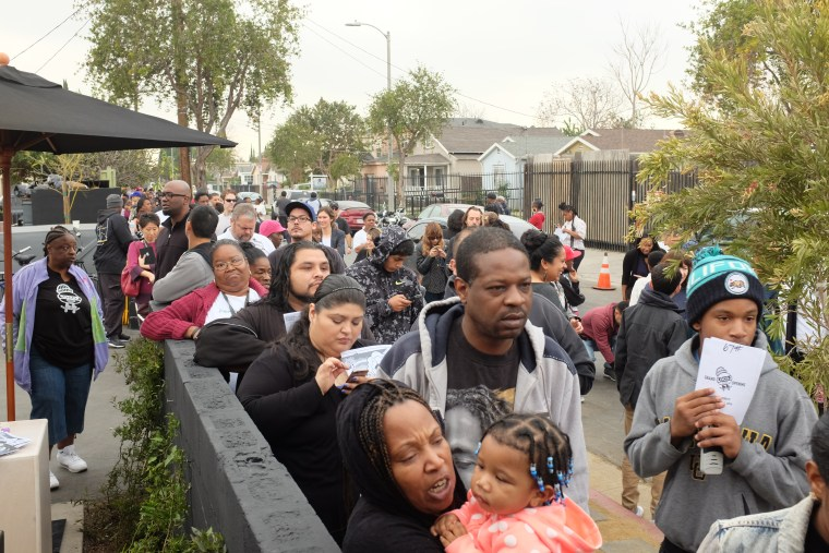 Hundreds of people wait to enter LocoL near the corner of Anzac Avenue and East 103rd Street in Watts, Los Angeles.