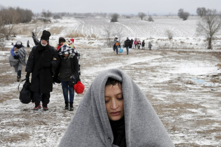 Image: Migrants walk through a frozen field after crossing the border from Macedonia