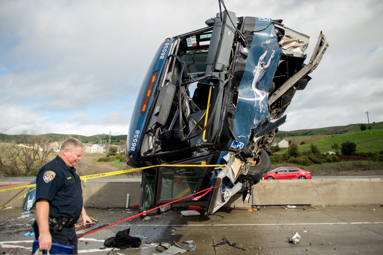 Image: A California Highway Patrol officer moves belongings from a Greyhound bus crash that left two dead