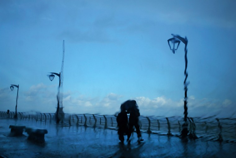 Image: A couple stands under an umbrella to shield themselves from heavy rain