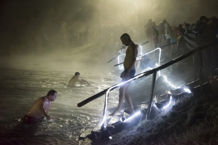 Image: Russian Orthodox believers bathe in ice water in a pond to mark Epiphany
