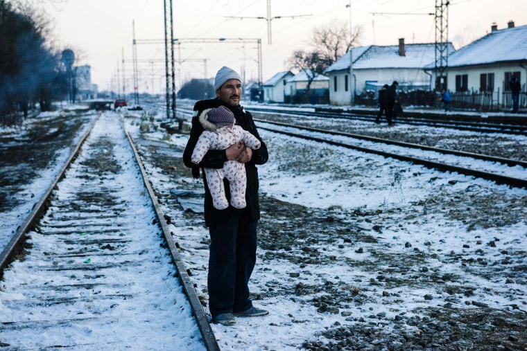 Image: A man holds his baby while waiting with other migrants and refugees at a train station in the Presevo
