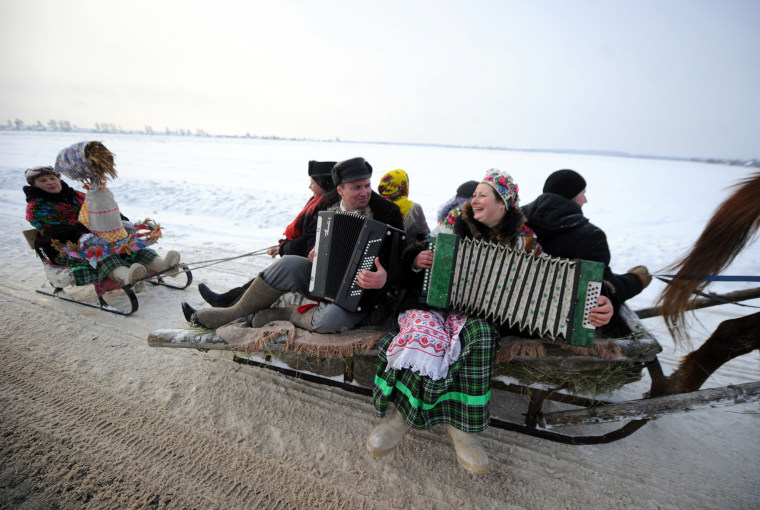 Image: A man and a woman play their accordions and sing as they ride a horse drawn sleigh celebrating the Kolyada holiday