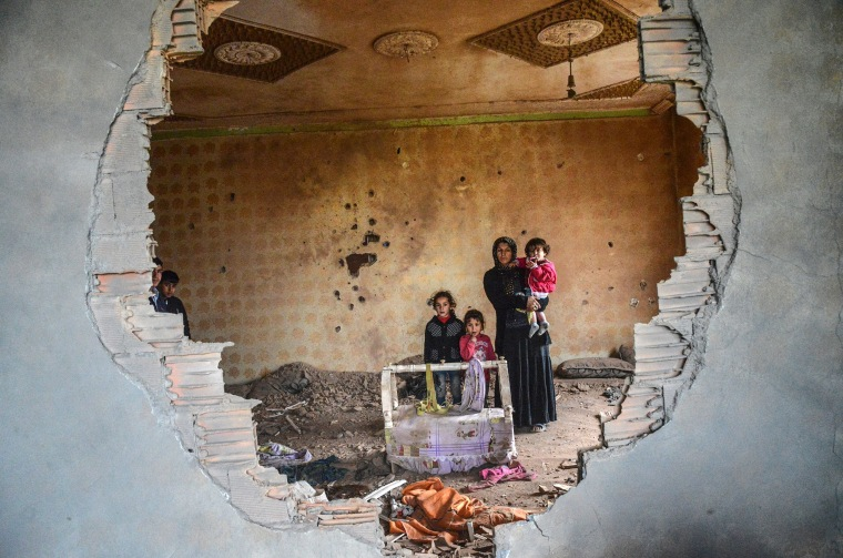 Image: A women and her children stand in the ruins of battle-damaged house in the Kurdish town of Silopi