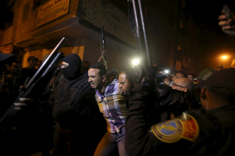 Image: Security forces detain a man at the scene of a bomb blast in a main street in Giza