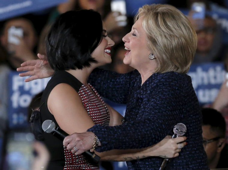 Image: U.S. Democratic presidential candidate Hillary Clinton is greeted by singer Demi Lovato as she arrives at a campaign event in Iowa City