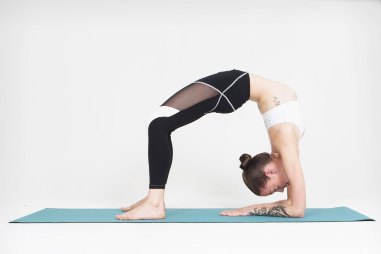 A model strikes a bridge pose wearing a pair of Nadi Smart Fitness Pants.