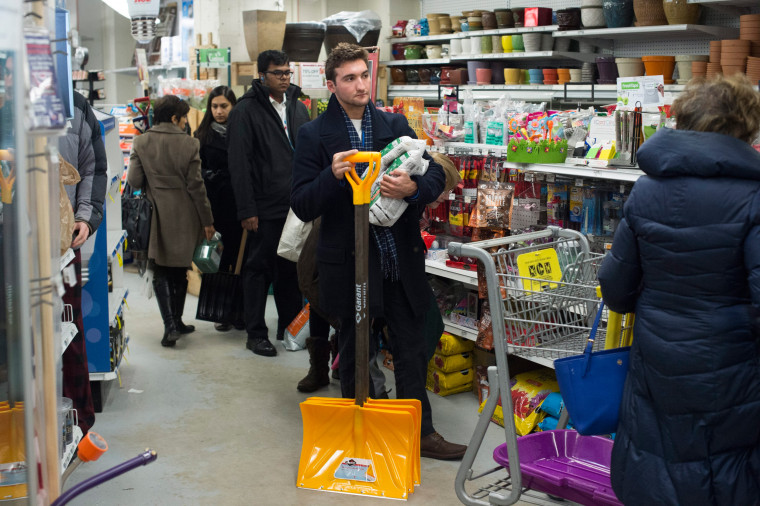 Image:  A customer waits in a line to purchase shovels and ice melt