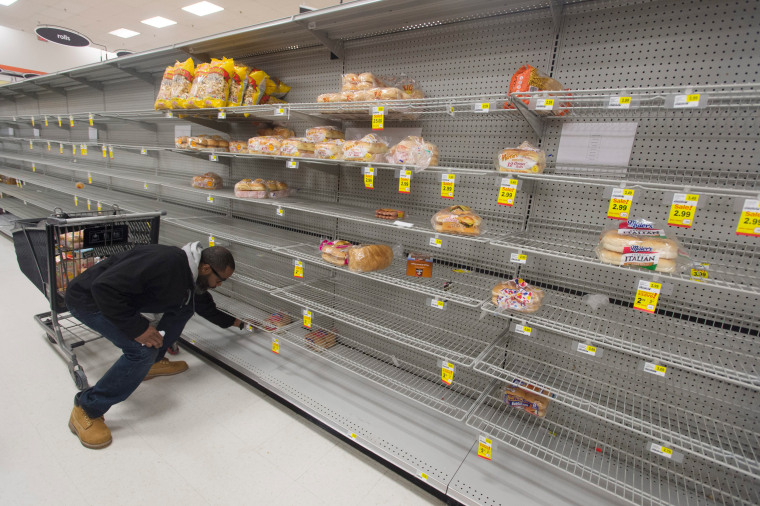 Image: A customer looks at the heavily depleted bread section of a grocery store