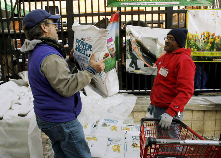Image: An employee watches a customer carry out a bag of ice melt