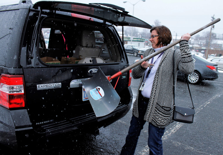 Image: A woman loads a newly purchased snow shovel into her SUV