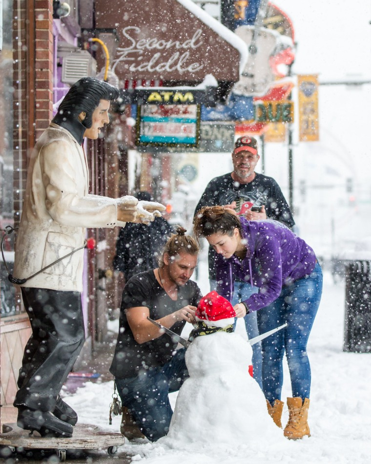Image: People decorate a snowman in Nashville