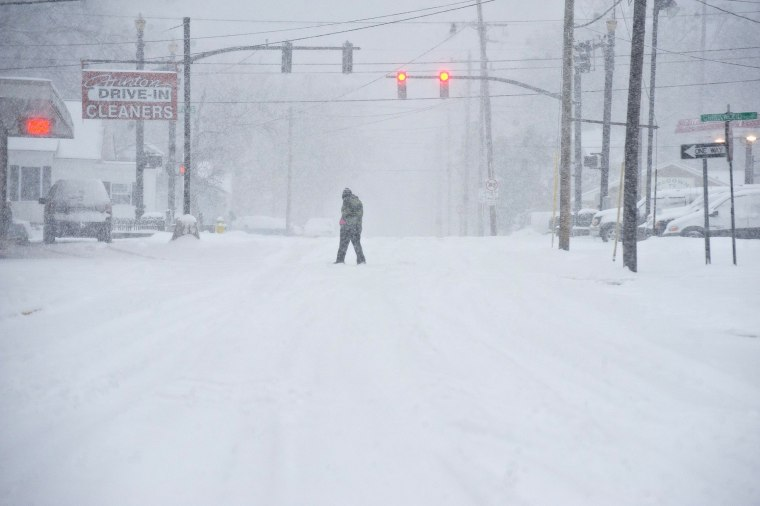 Image: A person walks through the blowing snow in Bowling Green, Ky.